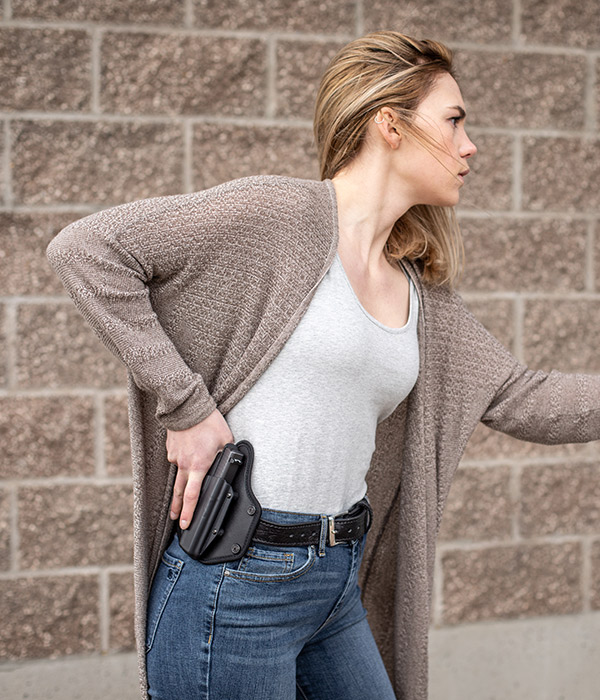 woman drawing gun from owb holster